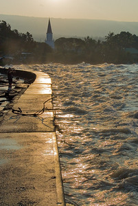 This and the next shot was taken standing on the Ali Drive seawall at the very height of a wave cresting, looking east towards sunrise and the Kailua church. I must admit that it was pretty foolish of me to stand here as several waves did previously crest over this wall. But I felt safer then the fellow-fool in the background standing below sea-level of all that water and energy...