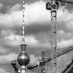 Berlin's Fernsehturm stands surrounded by construction cranes.