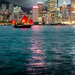 A junk drifts the waters beneath the skyline of Hong Kong Island.
