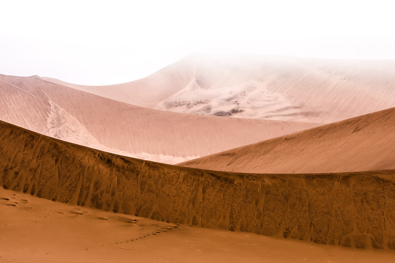 The dunes of the Namib desert owe their distinctive red hue to high concentrations of iron oxide, swept downstream from the Kalahari over millions of years. The heavier iron-rich deposits settle lower on the dunes as the winds lift lighter sands over the surface of the constantly shifting landscape.