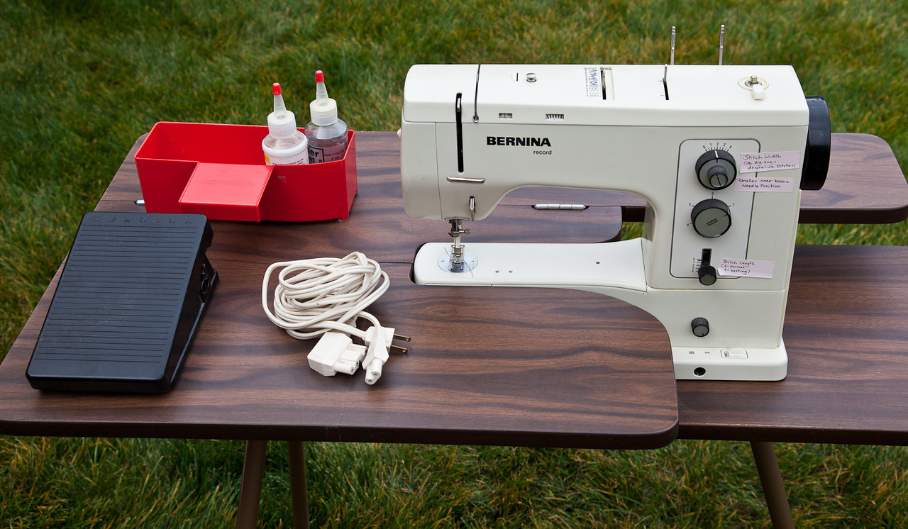 Click on the image to enlarge it. The machine in the table with the control pedal, cord, and storage box.