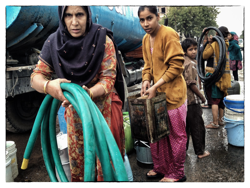 Delhi, India, Feb 2013 -   Women and children seen collecting water  from a water tanker in south Delhi.       Images for the Global Post's special report -   The Great Divide:  Global income inequality and its cost    Photograph:  Sami SIVA