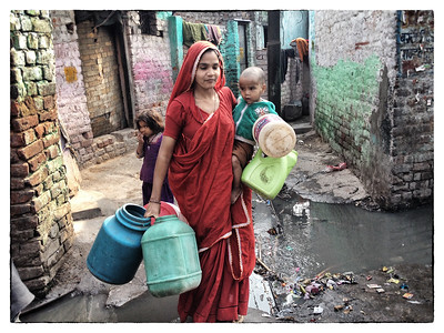 Delhi, India, Feb 2013 -    Women seen with her water buckets during a day in kathputli colony, a slum in New Delhi known for its artisans and puppeteers from Rajasthan. Access to water in the colony is limited to siphoning water off  the community taps.   Real estate developer - Raheja builders schedule to  rehabilitate the slum by building  a multi level apartments for the residents along with commercial and residential apartment complexes.   Images for the Global Post's special report -   The Great Divide:  Global income inequality and its cost    Photograph:  Sami SIVA
