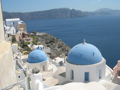 The town of Oia on Santorini with its traditional Cycladic architecture of blue-domed churches. Firastephanie and Thira are in the far distance on the other side of the caldera.
