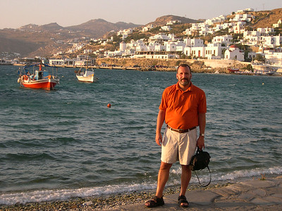 Joe, harborfront in Mykonos Town around sunset. The Tago district (where our hotel is) is on the hillside directly behind him.