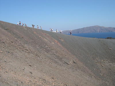 Here we climb the path that leads around the edge of the crater of the Nea Kameni volcano. The towns of Thira and Firastephanie can be seen in the background.