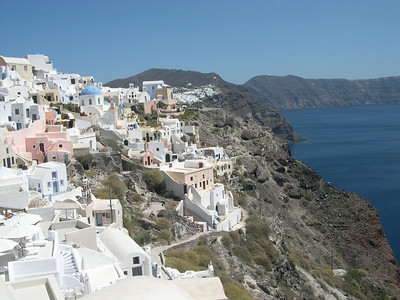 The beautiful town of Oia with its traditional Cycladic architecture on the tip of the island of Santorini. Looking across the caldera, you can see the edge of Firastephanie in the far distance.