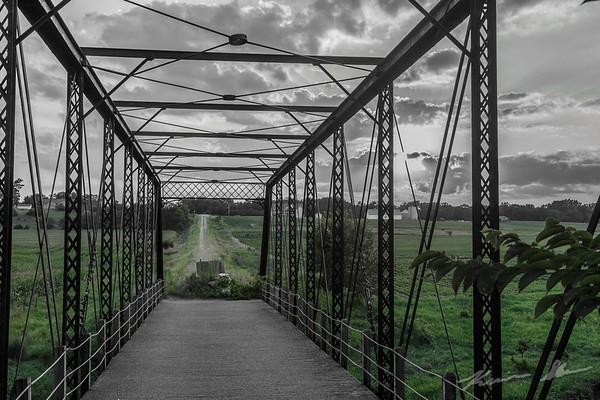 A beautiful summer sunset through a vintage 1880 truss bridge