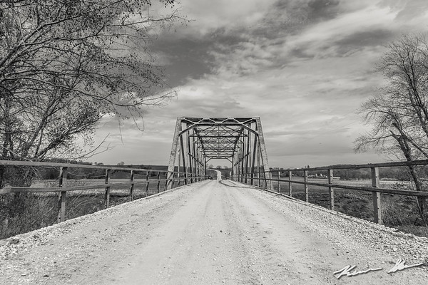 A worn steel truss bridge dating back to the early to mid 1900s crossing the placid Nodaway River