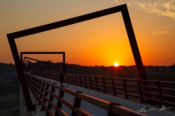 The setting sun through the High Trestle Bridge