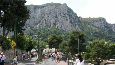 Via Roma in Capri, with the mountainous terrain of Monte Solano in the background.