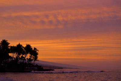This is the second in a series of shots taken as a storm front was moving in and the high cirrus clouds were lit-up by the sunrise over Hualalai volcano. This is the view looking south from the pier in Kailua-Kona towards the Kona Inn.