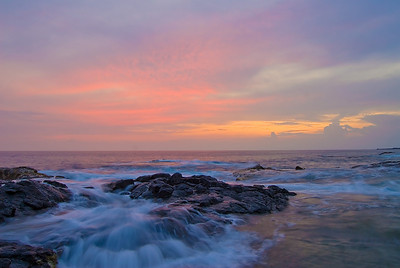 This is a typical soft sunset in Kona characterized by the pastel-looking colors created by the ever-present vog. This was shot at Shark's Hole - a locally popular swimming hole located at Old A's just north of Kailua-Kona.