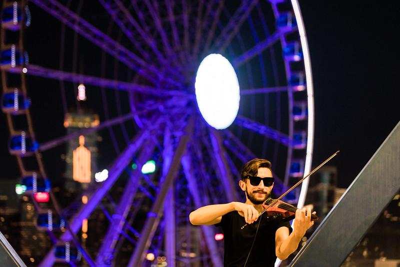 A street musician performs atop a skybridge overlooking the Hong Kong Observation Wheel.