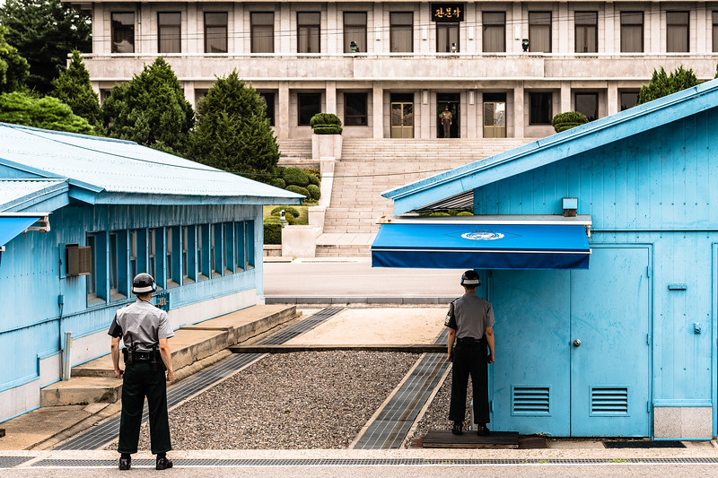 North and South Korean soldiers face off within the Korean Demilitarized Zone. The DMZ extends the full length of the de facto inter-Korean border and has been sown with an estimated one million land mines. Its 250km run is interrupted at only one point: the Joint Security Area, a setting of extraordinary tension, where negotiations may be held between the two countries. The short cement barrier running between the blue JSA buildings represents the Military Demarcation Line -- before it lies South Korea, beyond it North.