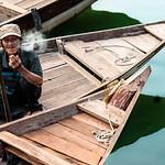 An elderly boat pilot enjoys a cigarette as evening falls on Hoi An.