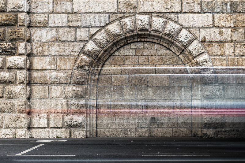 A speeding vehicle streaks past an old archway on Budapest's Danube bank.
