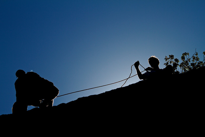 Belaying a climber at Hueco Tanks.