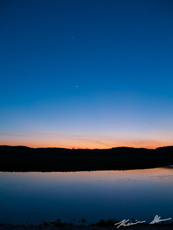 A waxing crescent moon with Venus (above) and Jupiter (on the horizon) over the Des Moines River