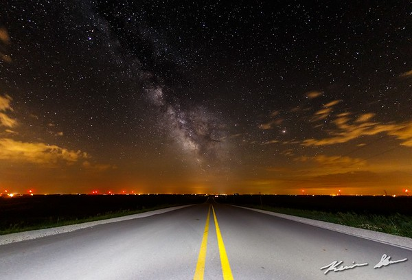 Mily Way rises over a lone Iowa county road
