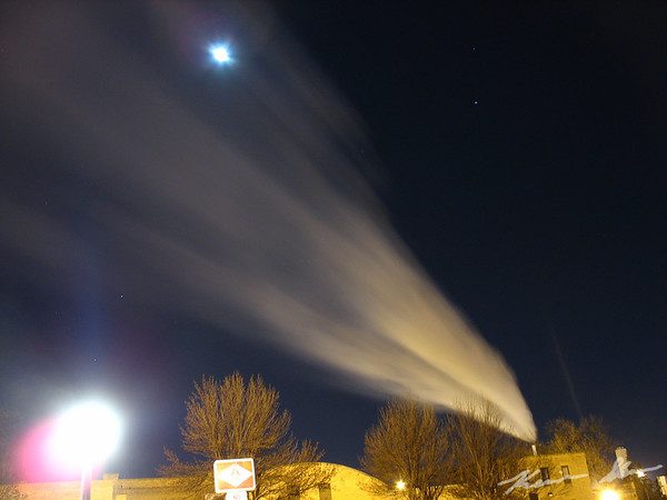 A steam plume from the UND campus powerplant drifts across the moonlit sky