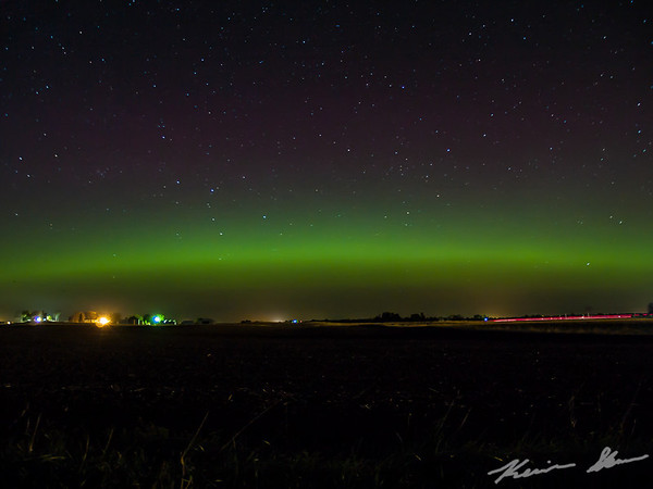 A dim auroral banner draped across the northern Iowa sky