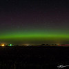 A dim auroral banner draped across the northern Iowa sky