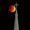Total lunar eclipse passes by a church steeple.