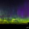 A small meteor streaks through the dancing aurora pillars