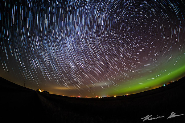 The stars racing across the night sky as an aurora glows to the north