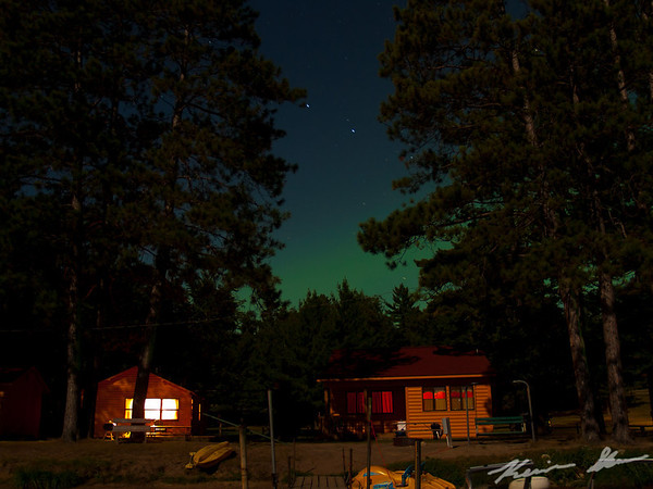 The aurora glows just over the cabin