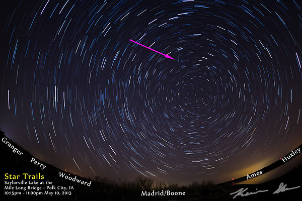 Star trails from Saylorville Lake, with an iridium flare passing through the photo (pink arrow). Lights from the surrounding cities are also highlighted