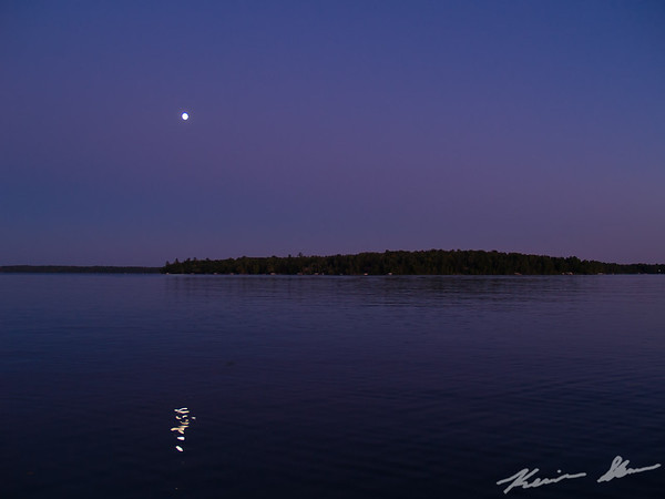An evening fishing with a beautiful full moon on a placid lake