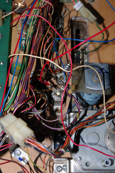 Last, we get power and signal from the lower right flasher.The bulb is to the left of the idol lock solenoid. It might be best to undo the mounting screw so that you can solder away from the little forest of wires! Run the red and blue wires up the playfield, following the flasher loom, to keep everything tidy. You can see the route on the main picture.