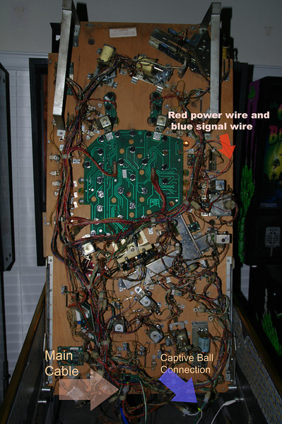 Start by hooking the long shaker control cable into the main cable entry in the middle of the bottom of the playfield. You'll set it up so the connectors are above the cable clip, which stops it from falling out. Run the long black wire up into the head and secure it to the ground point.