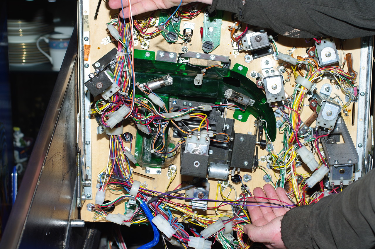 Running the Wires<br /> Connect the playfield harness to the cabinet harness. The black and purple wires should run along the bottom edge of the playfield. The 4-pin harness, red (picture is incorrect), and blue wires should run up the side. Dress these wires into the harness as they are connected.