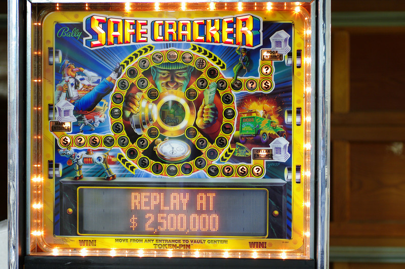 Safecracker backbox. The backbox houses a board game and the token deliver mechanism. The ropelight uses flasher circuits. The board game has an entire circuit board of its own, and is separate from the lamp matrix. <br /> Safecracker has more controlled lights than any other pinball machine. It also uses pretty much every solenoid, flasher and flipper circuit.