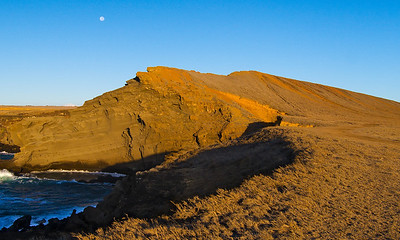 A morning  view of Pu'u O'Mahana cinder cone which overlooks Green Sands (Papakolea) beach in the Ka'u district on the southeast coast of Hawaii. I liked the moon setting in the background and the contrast between the harsh landscape and the blue sky and ocean...