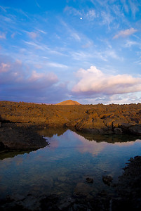 One of my favorite photos, this was shot at the end of the Road-to-the-Sea in the Manuka Natural Area Preserve on the southwest coast of Hawaii. The moon is seen rising over Na Pu'u a Pele cinder cone with the sky reflected in a fresh water pond formed in the jagged A'a lava.