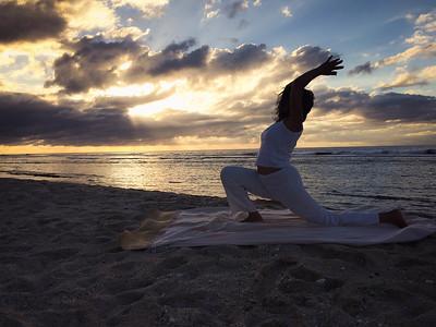 La salutation au soleil sur une plage à la Réunion