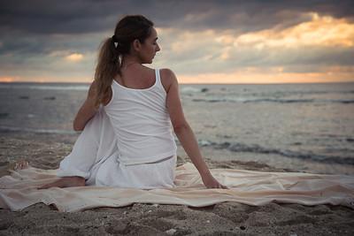La posture de la torsion (Vakrasana) sur une plage à la Réunion