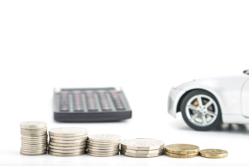 Stacks of Coins with Calculator and Car in the Background