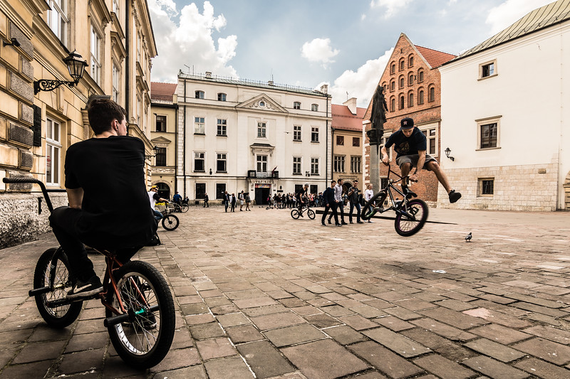 BMX riders practice amid the pedestrian traffic on Krakow's plac Marii Magdaleny.