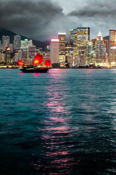 A junk drifts the waters beneath the skyline of Hong Kong Island.