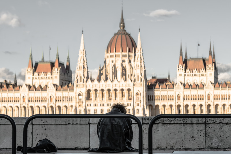 A homeless man sits in shadow opposite the Hungarian parliament.