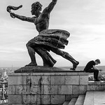 A young man sits with his back to a victory statue atop Budapest's Gellért hill.