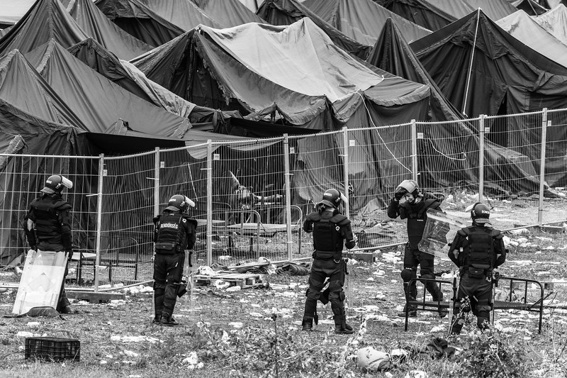 Hungarian police in riot gear stand guard outside a makeshift refugee internment camp near Röszke on September 5, 2015.