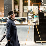 An orthodox priest strolls past the works of one of Belgrade's young painters.