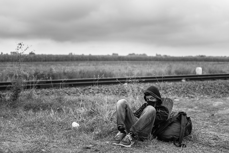 A refugee boy sits beside the railway tracks outside Röszke, detained in an improvised holding area by Hungarian police on September 5, 2015.