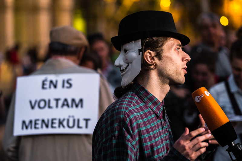 "On the eve of the October 2, 2016 referendum on refugee issues in Hungary, a young political organiser wearing an Guy Fawkes mask gives an interview to a German television broadcaster. Behind him, an elderly gentleman wears a billboard which reads ""I too was a refugee."""